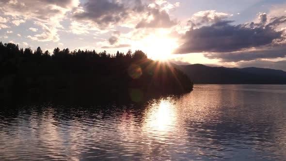 Thumbnail for Flying towards sunset over lake