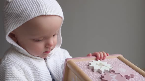 Thumbnail for Cute Baby In Knitted Sweater Playing With Wooden Toy.