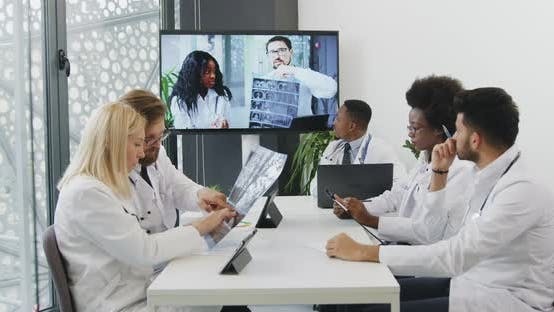 Thumbnail for Medical Workers Sitting Around Table in Office Room and Having Online Video Conference