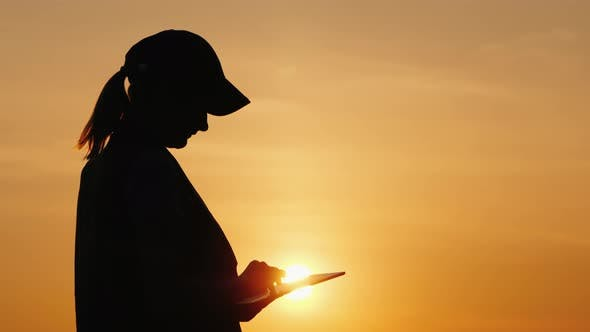 Thumbnail for Silhouette of a Woman Farmer Working with a Tablet at Sunset