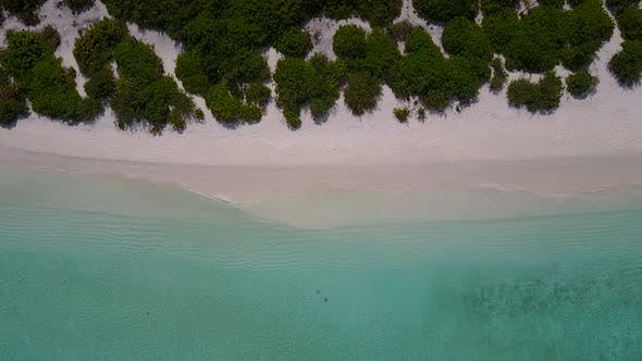 Aerial travel of coastline beach by lagoon with sand background
