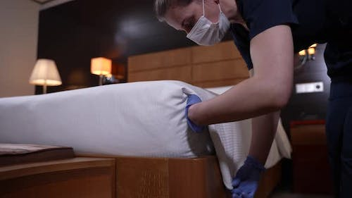 Neat Maid Straightening Edge of Blanket on Bed