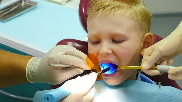 Thumbnail for Health Concept. Boy at Dental Clinic Gets Dental Treatment To Fill a Cavity in Tooth. Dental
