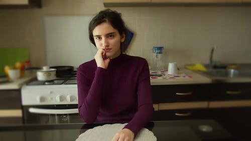 Portrait of a Pretty Brunette Girl in the Kitchen at the Table Sits Thinking