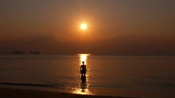 Thumbnail for Young Woman As Silhouette In The Sea At Sunset