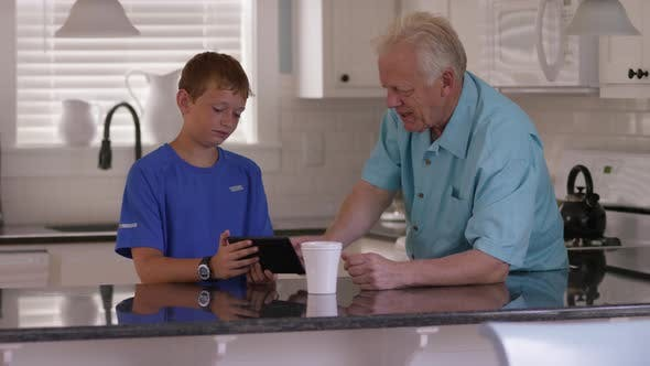 Thumbnail for Grandson showing grandfather how to use tablet