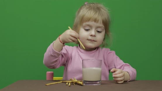 The Child Eats Cookies. A Little Girl Is Eating Cookies Sitting on the Table