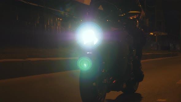 Mann reitet auf modernem Sportmotorrad mit nachts eingeschaltetem Scheinwerfer