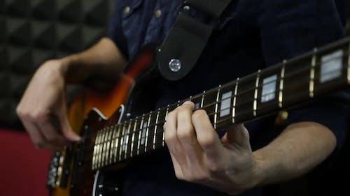Musician playing rock music on bass guitar
