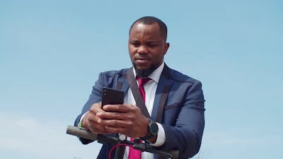 Confident Black Businessman on Escooter Using Cellphone