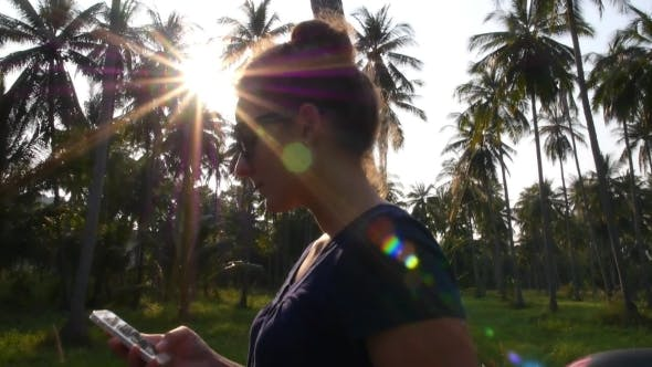 Thumbnail for Female Using Smart Phone Against Sun Beams