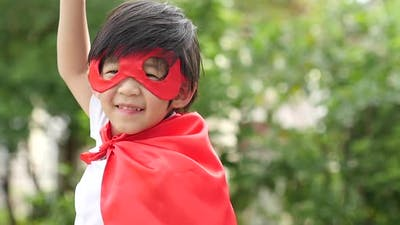 Asian Child In In Superhero Costume Playing In The Park