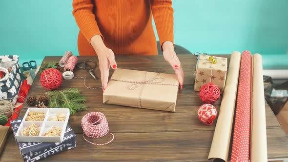 Thumbnail for Close up Female hands decorating gift red boxes for Christmas Holiday.