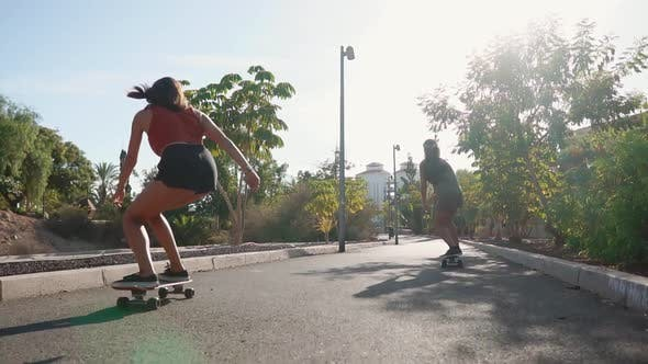 Cover Image for Summer on the Island of Young Girls on Longboard Rides in Short Shorts on the Road Near the Beach