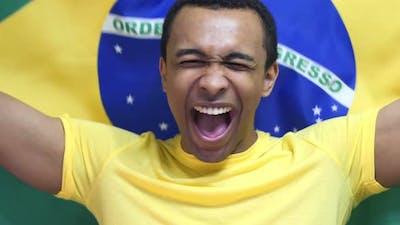Brazilian Fan Celebrates Holding the Flag of Brazil