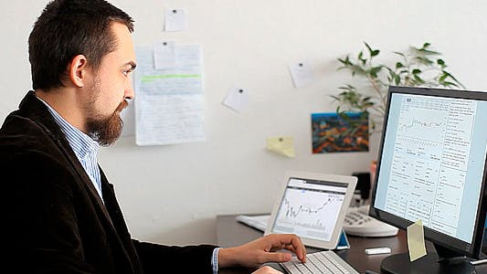 Thumbnail for Businessman Exploring Currency Exchange Charts