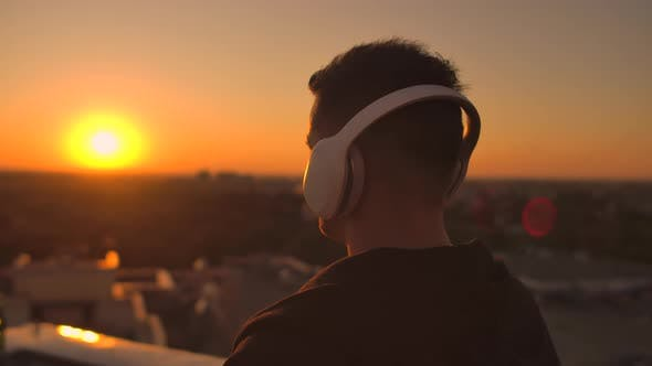 Thumbnail for A Man Walks on the Roof at Sunset with Headphones Looking at the City From the Height of a
