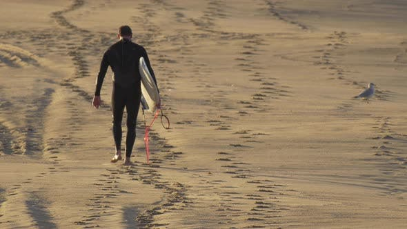 A surfer walking with his surfboard