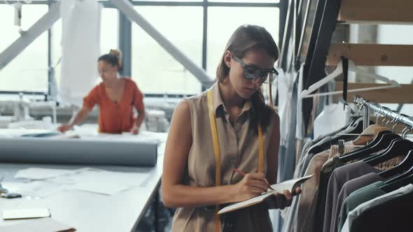 Thumbnail for Young Female Tailor Examining Clothes and Taking Notes in Studio