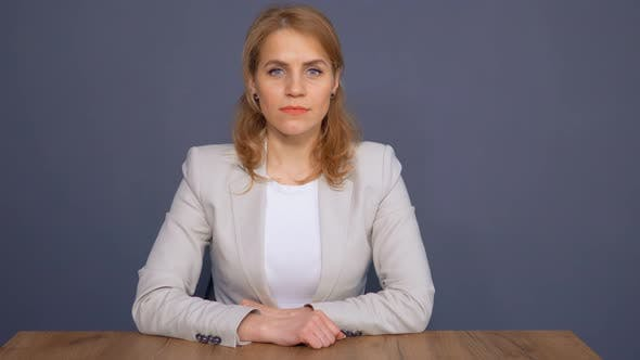 Thumbnail for Charming Blond Business Lady Is Sitting at Table on Studio Background