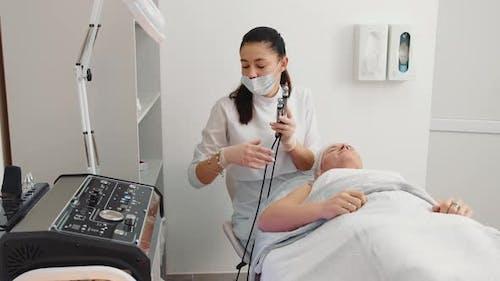 Die Kosmetikerin beginnt mit der Prozedur der Mikrostromtherapie in einem Schönheitssalon