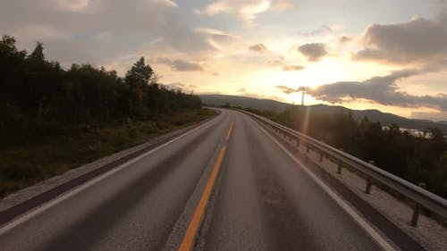 Driving a Car on a Road in Norway at Dawn