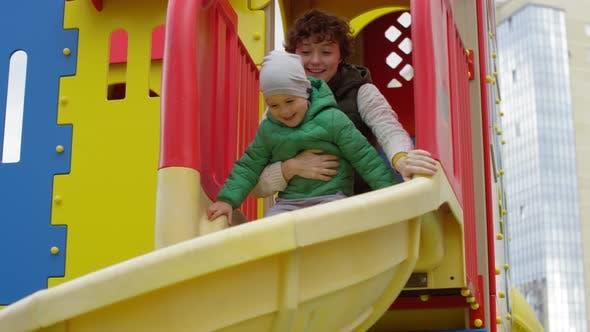 Junge kaukasische Familie mit Spaß zusammen auf Spielplatz Rutsche