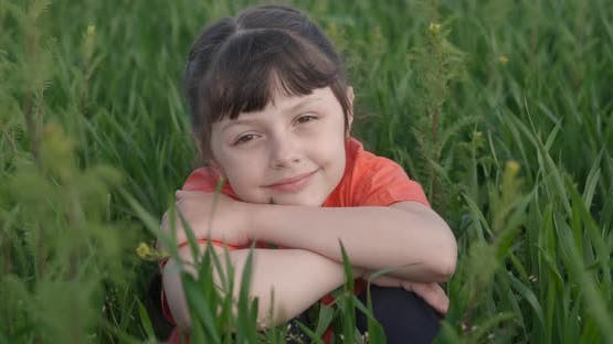 Child Sits in the Green Meadow