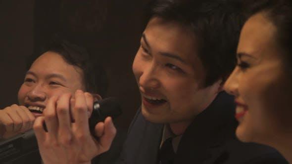 Males and female singing karaoke