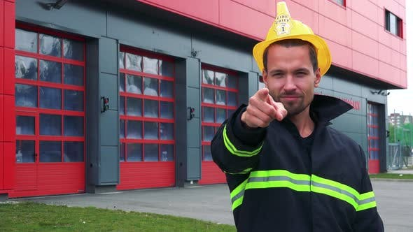 Cover Image for A Young Firefighter Points at the Camera and Nods - a Fire Station in the Background