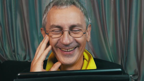 Thumbnail for Laughing Man in Glasses Reading a Tablet