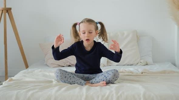 Kleines Mädchen meditiert in Lotus Position Drinnen