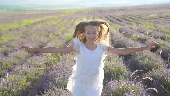 Thumbnail for Woman in Lavender Flowers Field at Sunset in White Dress and Hat