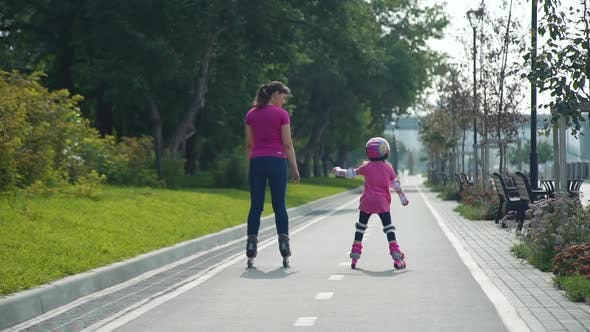 Little Girl with Mother Riding on Rollerblades