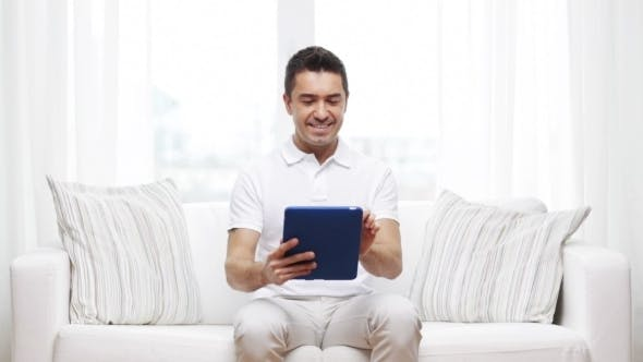 Thumbnail for Smiling Man Working With Tablet Pc At Home