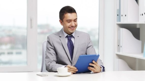 Thumbnail for Smiling Businessman With Tablet Pc Drinking Coffee