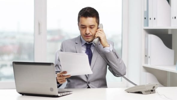 Thumbnail for Smiling Businessman With Laptop Calling On Phone