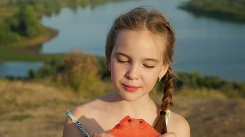 Little Girl with Plait Bites Juicy Watermelon on Riverbank