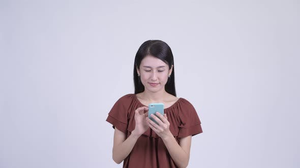 Thumbnail for Face of Happy Beautiful Asian Woman Using Phone and Looking Surprised