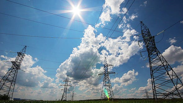 Thumbnail for Tall Electric Masts Against Sun And Cloudy Sky