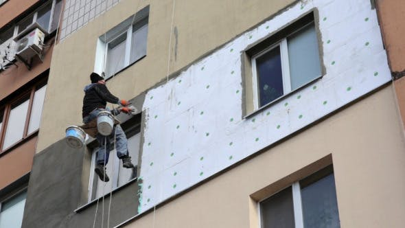 Worker Repairs the Facade