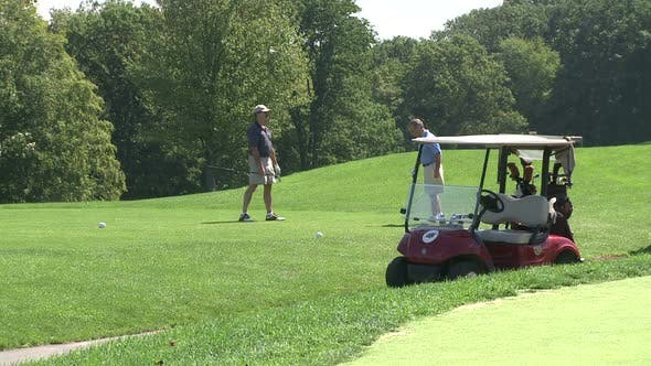 Thumbnail for Golf Cart Parked With Two Golfers On The Green (1 Of 2) 1