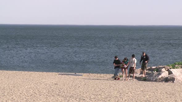 Thumbnail for Young People Walking Around The Rocks Along The Shore (1 Of 2)