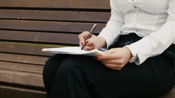 Cover Image for Closeup Of Business Woman Writing With Pen In A Notebook