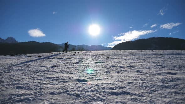 Thumbnail for Unrecognizable Guy Goes Nordic Walking with Sticks on Snowy Meadow at Sunny Day. Young Hiker Treks
