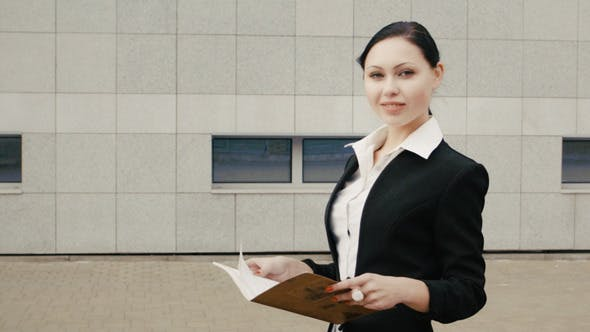 Thumbnail for Businesswoman In Black Suit Staying With Notebook