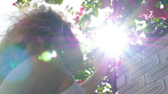 Thumbnail for Young Girl In Sun Beams Looking At Flowers
