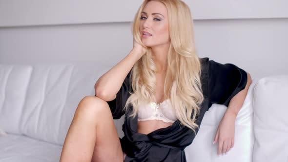 Thumbnail for Pretty Female In Sleepwear Sitting On White Sofa 1