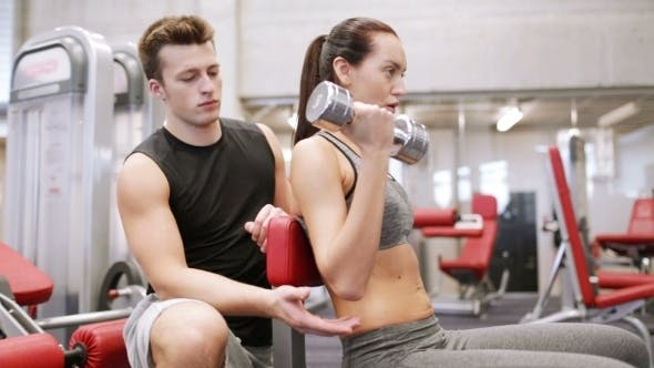 Thumbnail for Young Couple With Dumbbell Flexing Muscles In Gym