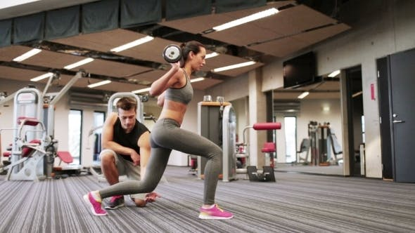 Thumbnail for Man And Woman With Barbell Flexing Muscles In Gym